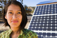 A happy smiling American Indian woman and solar panels in an environmental picture representing ecology, green living, renewable energy and living responsibly to protect the environment.